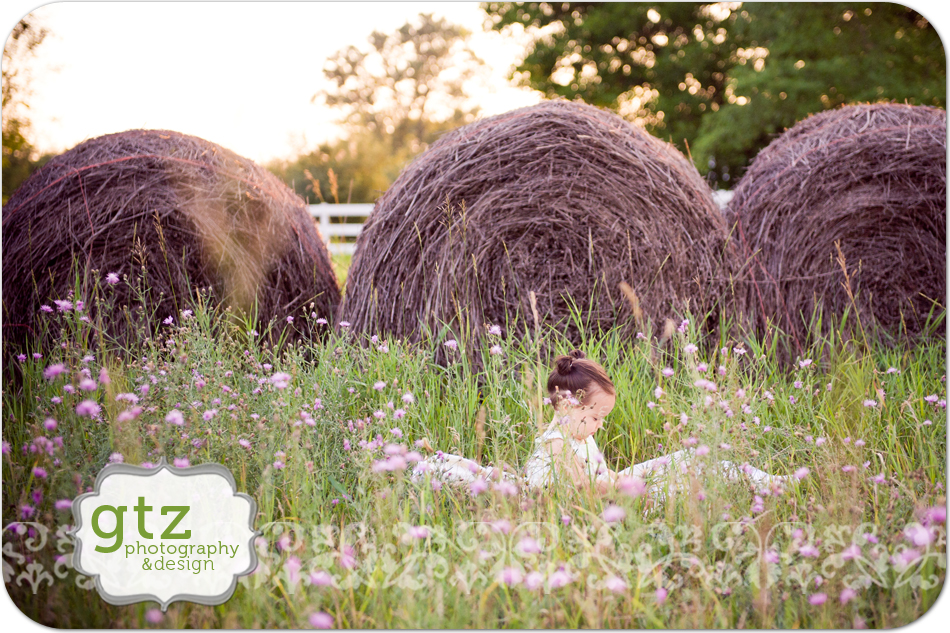 Baby girl in field with hay bales behind