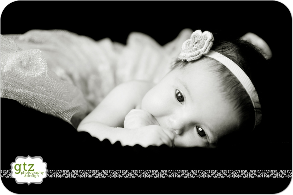 Newborn girl on black background wearing a tutu with a flower headband