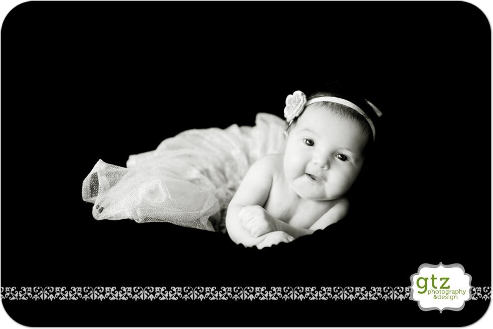 Newborn girl with tutu and flower headband lifting head