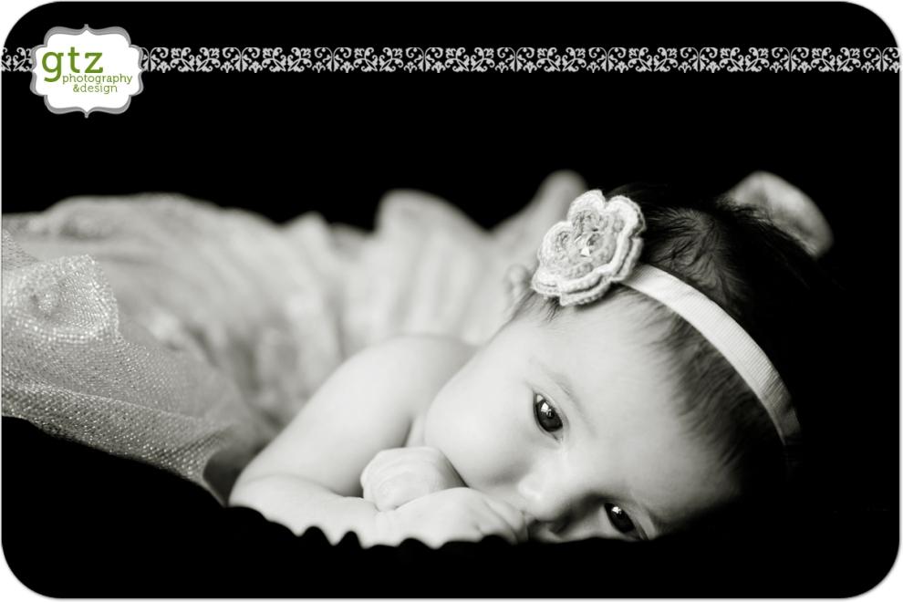 Newborn girl on tummy, with tutu and flower headband