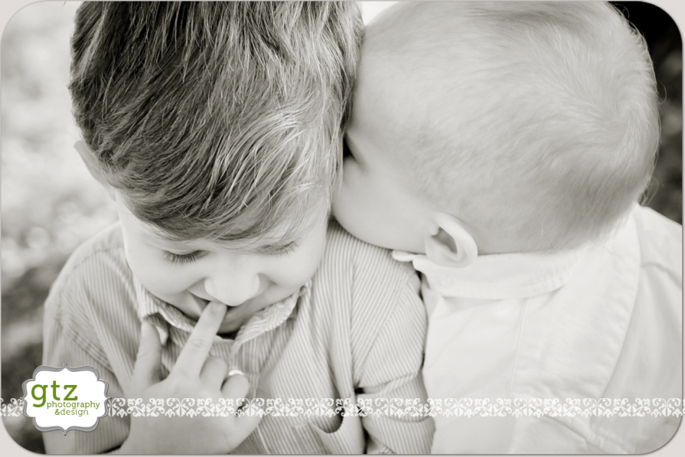 Baby boy gives his big brother a kiss on the cheek