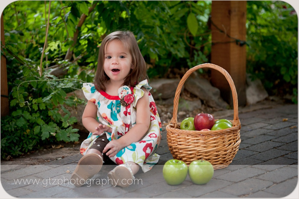 Two year old girl with basket of red and green apples