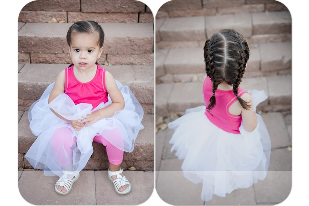 little girl in a tutu with braids on steps