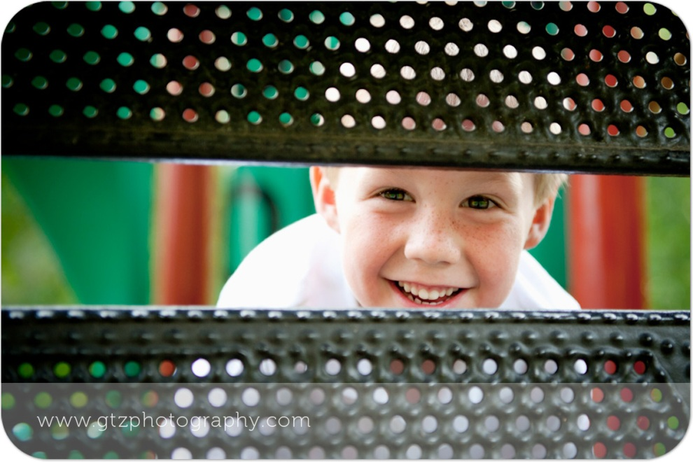 Little smiling boy peeking through playground equipment