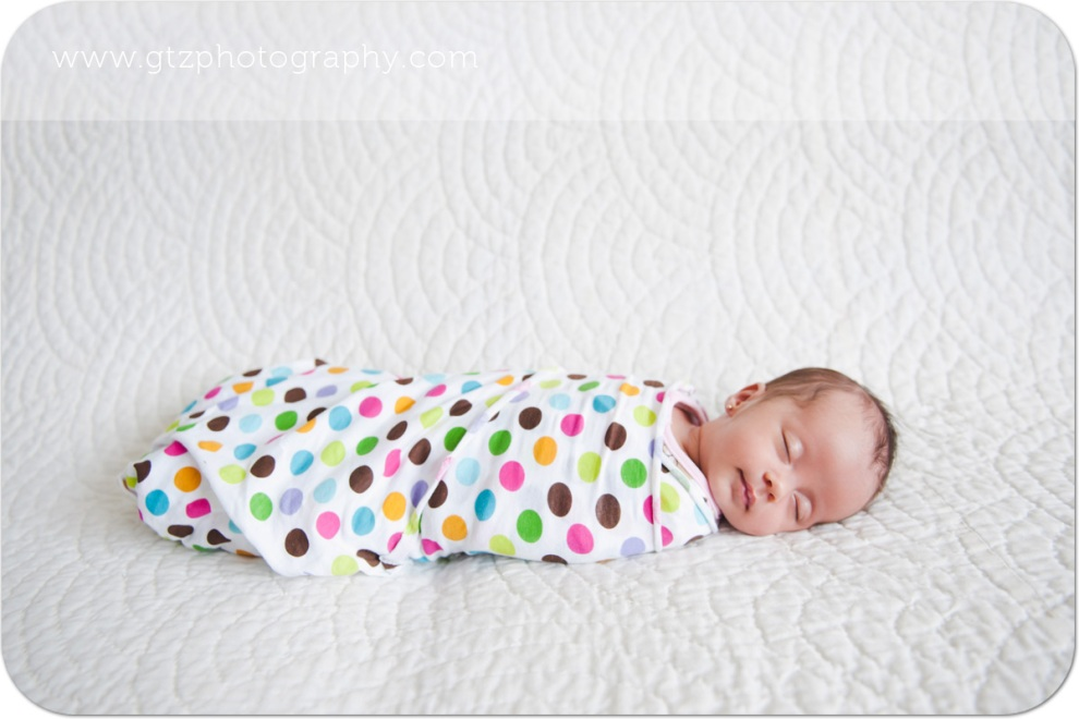 Newborn baby girl in polka dot wrap, sleeping