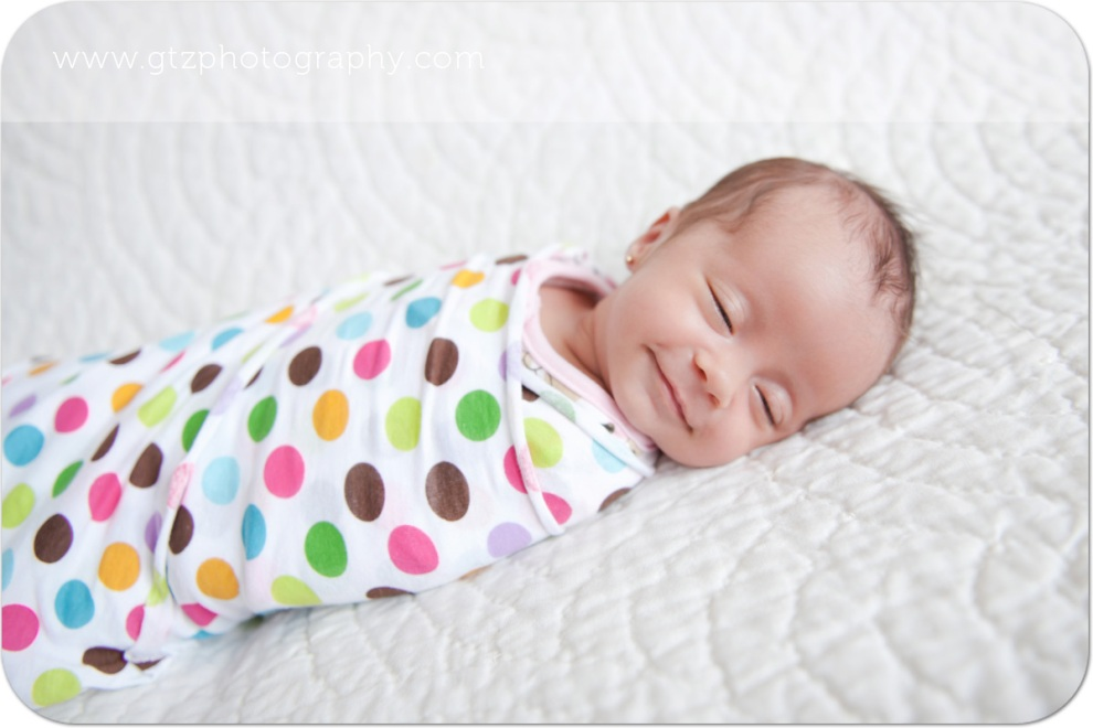 Newborn baby girl in polka dot wrap, smiling with eyes closed