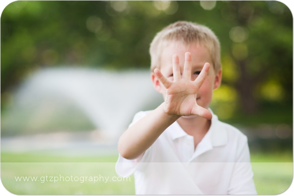Little boy holding up five fingers for five years old