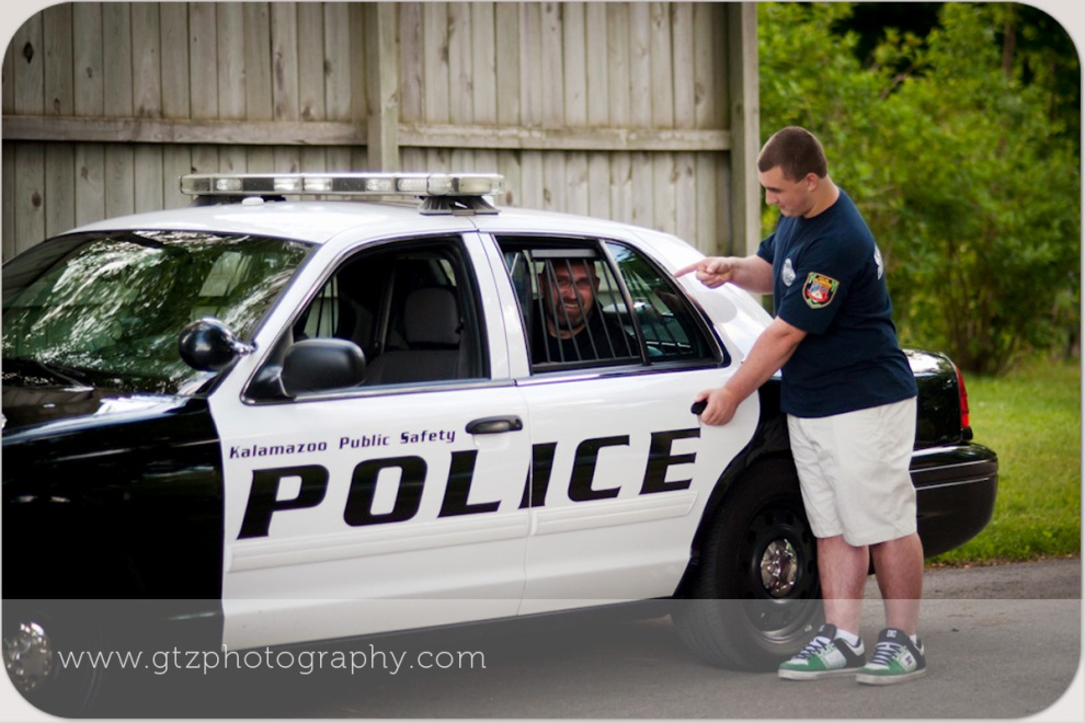 High School Senior Boy Humorous Portrait with Dad in back of squad car