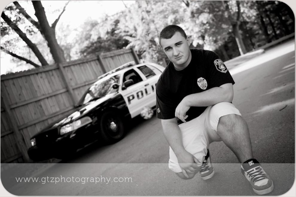 High school senior boy portrait with police car in background