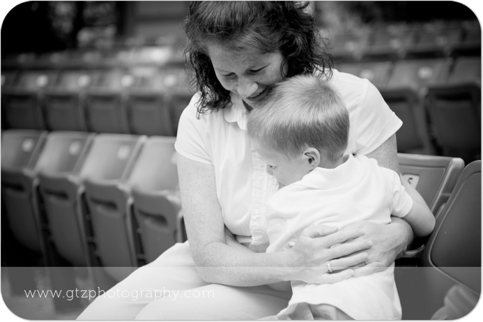 Black and white image of little boy hugging his mommy