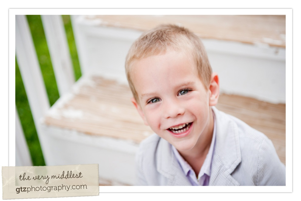 three year old boy sitting on steps smiling up at camera