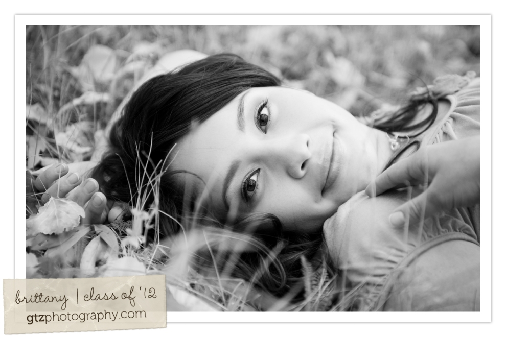 high school senior girl portraits black and white lying on back in grass