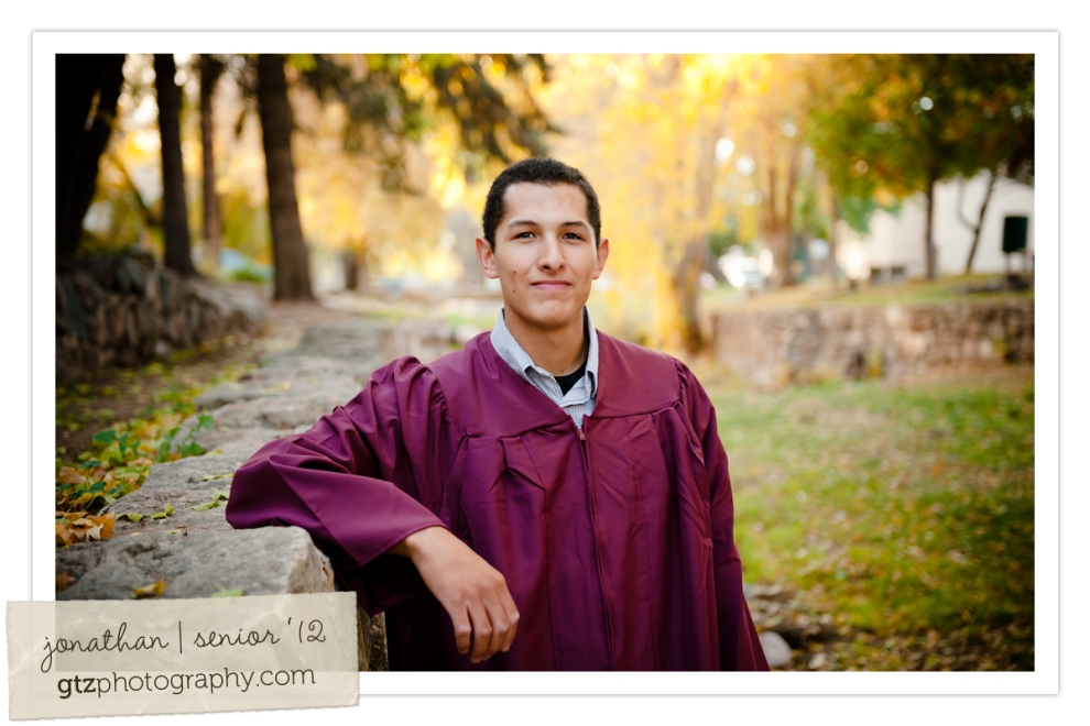 high school senior guy portrait in graduation gown in santa fe riverbed new mexico