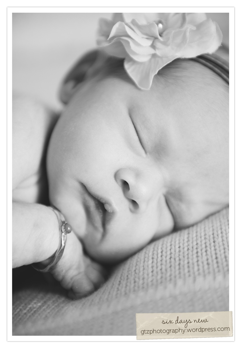 six day old newborn baby girl, closeup of sleeping face, with flower headband and bracelet